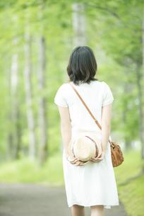 森林の中を歩く女性の後姿の写真素材 [FYI04548579]