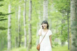 スマートフォンで電話をする女性の写真素材 [FYI04548585]
