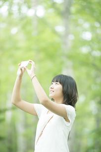スマートフォンで写真を撮る女性の写真素材 [FYI04548603]