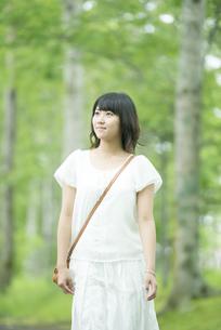 森林の中を歩く女性の写真素材 [FYI04548604]