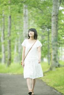 森林の中を歩く女性の写真素材 [FYI04548605]