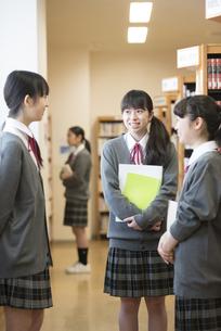 図書室で談笑をする女子学生の写真素材 [FYI04548652]