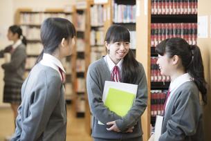 図書室で談笑をする女子学生の写真素材 [FYI04548655]
