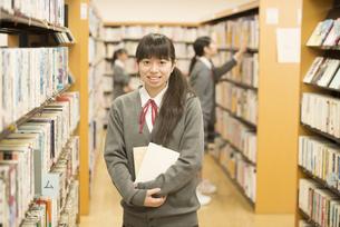 図書室で本を持ち微笑む女子学生の写真素材 [FYI04548660]