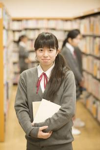 図書室で本を持ち微笑む女子学生の写真素材 [FYI04548661]