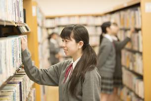 図書室で本を選ぶ女子学生の写真素材 [FYI04548667]