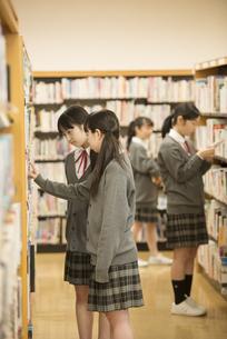 図書室で本を選ぶ女子学生の写真素材 [FYI04548674]
