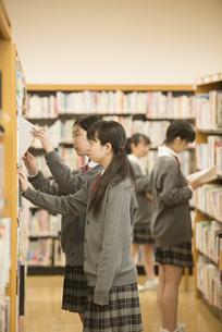 図書室で本を選ぶ女子学生の写真素材 [FYI04548676]
