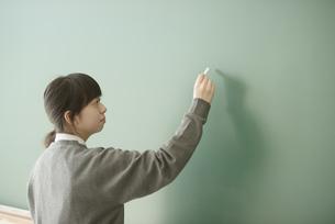 黒板に文字を書く女子学生の写真素材 [FYI04548708]