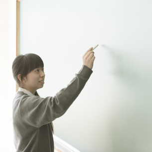 黒板に文字を書く女子学生の写真素材 [FYI04548709]