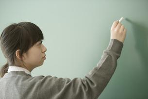黒板に文字を書く女子学生の写真素材 [FYI04548710]