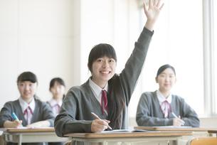 教室で手を挙げる女子学生の写真素材 [FYI04548769]