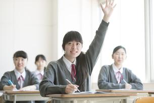 教室で手を挙げる女子学生の写真素材 [FYI04548770]