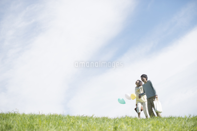 草原で風船を持ち微笑むカップルの写真素材 [FYI04548790]