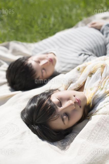 草原で眠るカップルの写真素材 [FYI04548796]