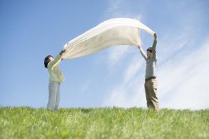 草原で布を広げるカップルの写真素材 [FYI04548805]