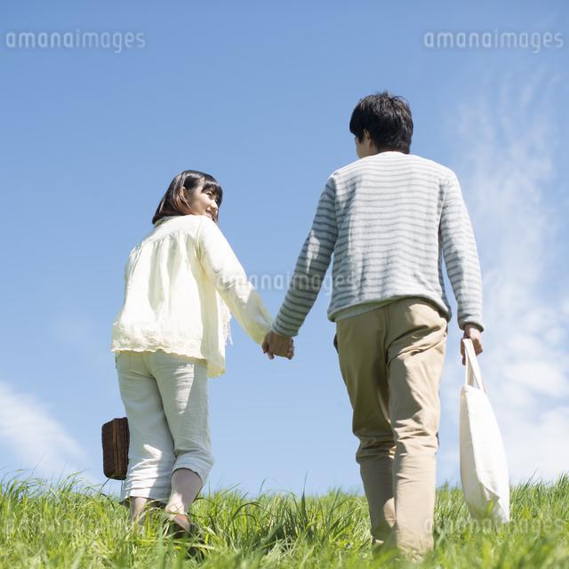 草原で手をつなぐカップルの後姿の写真素材 [FYI04548826]