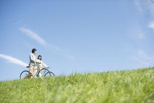 草原で自転車を押すカップルの写真素材 [FYI04548843]