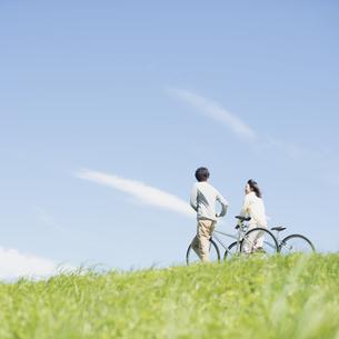 草原で自転車を押すカップルの写真素材 [FYI04548850]