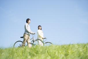 草原で自転車を押すカップルの写真素材 [FYI04548855]