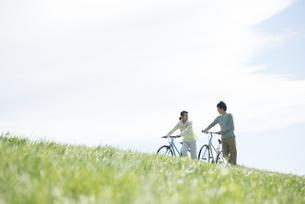 草原で自転車を押すカップルの写真素材 [FYI04548864]