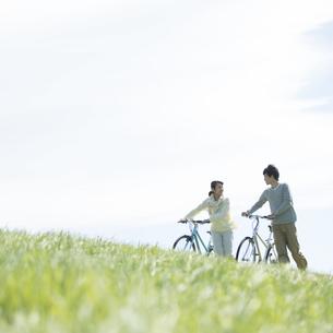 草原で自転車を押すカップルの写真素材 [FYI04548869]