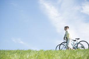 草原で自転車を押すカップルの写真素材 [FYI04548874]