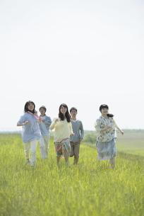 草原を走る大学生の写真素材 [FYI04548907]