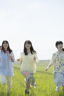 草原を走る大学生の写真素材 [FYI04548909]