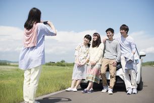 車の周りで写真を撮る大学生の写真素材 [FYI04548916]