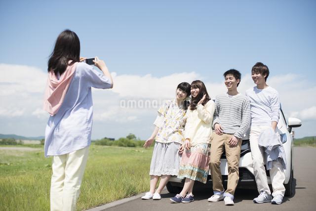 車の周りで写真を撮る大学生の写真素材 [FYI04548920]