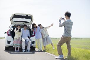 車の周りで写真を撮る大学生の写真素材 [FYI04548923]