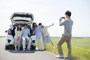 車の周りで写真を撮る大学生の写真素材 [FYI04548925]