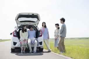車の周りで談笑をする大学生の写真素材 [FYI04548927]
