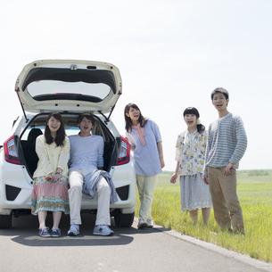 車の周りで微笑む大学生の写真素材 [FYI04548930]