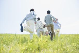 草原を走る大学生の後姿の写真素材 [FYI04548940]