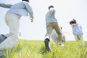 草原を走る大学生の後姿の写真素材 [FYI04548943]