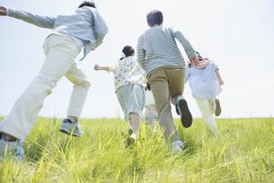 草原を走る大学生の後姿の写真素材 [FYI04548945]