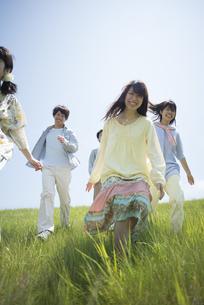 草原を走る大学生の写真素材 [FYI04548949]