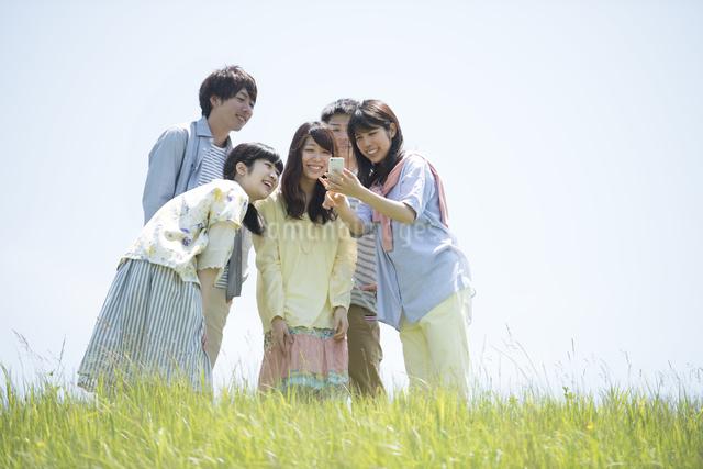 草原でスマートフォンを見る大学生の写真素材 [FYI04548958]