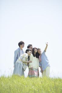 草原で自分撮りをする大学生の写真素材 [FYI04548963]