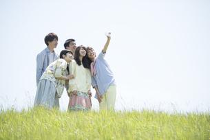 草原で自分撮りをする大学生の写真素材 [FYI04548964]