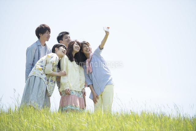 草原で自分撮りをする大学生の写真素材 [FYI04548965]