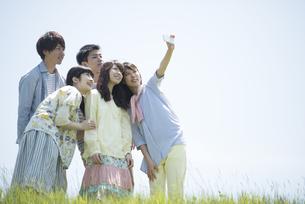 草原で自分撮りをする大学生の写真素材 [FYI04548967]