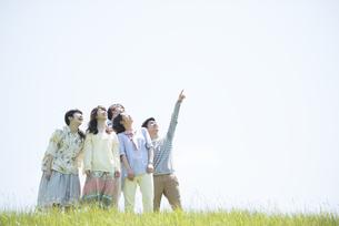 草原で空を見上げる大学生の写真素材 [FYI04548970]