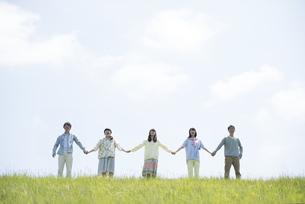 草原で手をつなぐ大学生の写真素材 [FYI04548980]