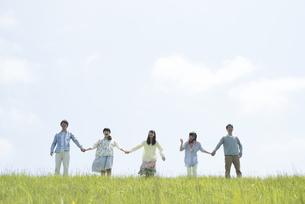 草原で手をつなぐ大学生の写真素材 [FYI04548981]