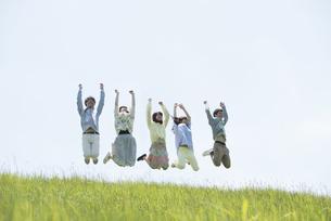 草原でジャンプをする大学生の写真素材 [FYI04548984]
