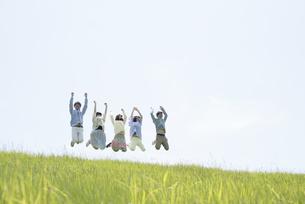 草原でジャンプをする大学生の写真素材 [FYI04548985]