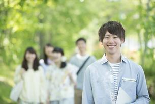 新緑の中で微笑む大学生の写真素材 [FYI04549001]